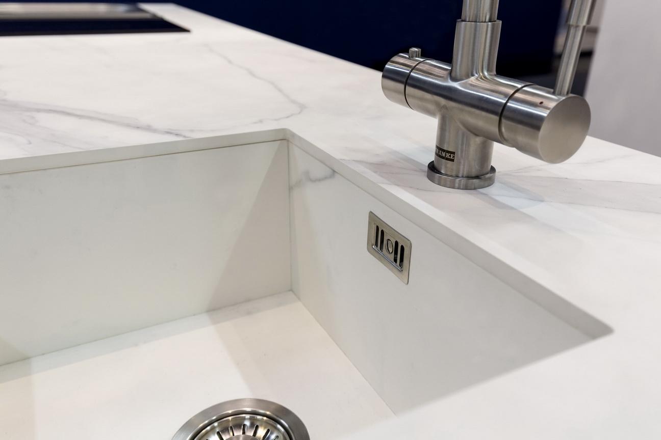 חדר אמבטיה- כיור לבן ומשטח נאוליט לבן עם עורקים עדינים בצבע כהה